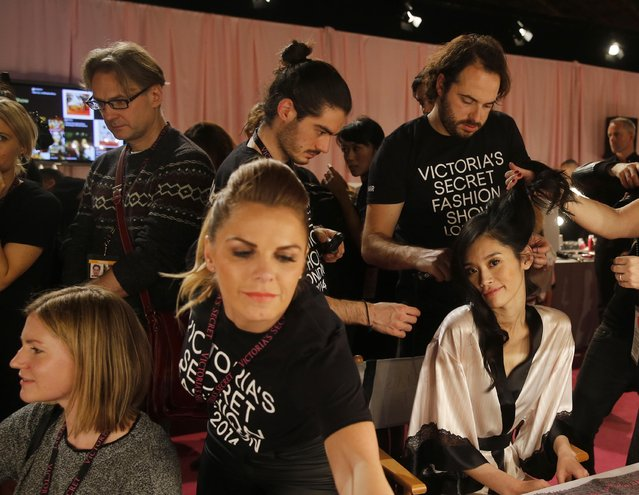Assistants help models prepare backstage ahead of the 2014 Victoria's Secret Fashion Show in London December 2, 2014. (Photo by Suzanne Plunkett/Reuters)
