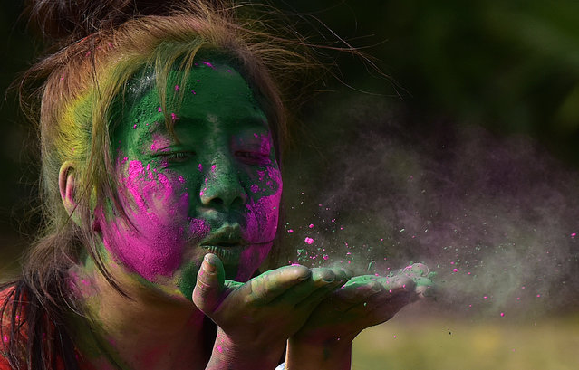 People playing with colours to celebrate Holi at GIP Mall on March 1, 2018 in Noida, India. (Photo by Virendra Singh Gosain/Hindustan Times via Getty Images)
