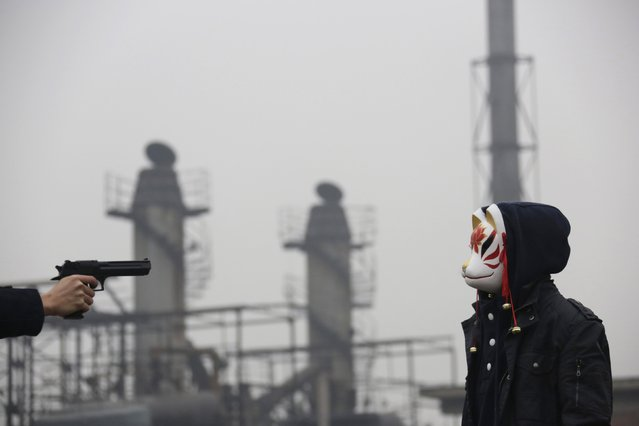 A performer wearing a mask takes part in a short film production on a hazy day at Beijing's 798 art zone, November 29, 2014. (Photo by Jason Lee/Reuters)