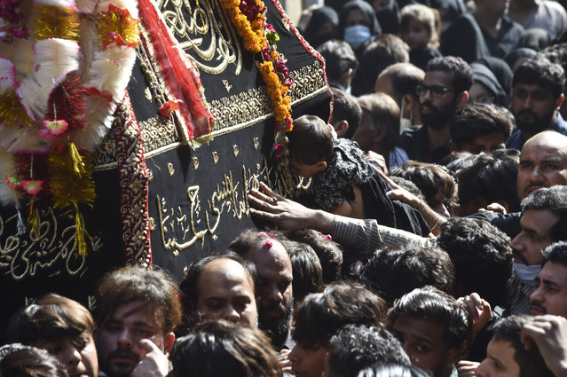 Shiite Muslims take part in a religious procession to mark the 40th day of mourning after the death anniversary of Imam Hussain, the grandson of the Prophet Mohammed, in Lahore on October 8, 2020. (Photo by Arif Ali/AFP Photo)