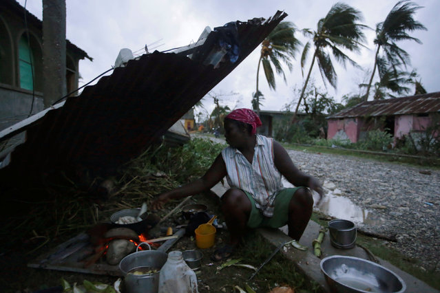 A woman cooks next to a house damaged by Hurricane Matthew in Les Cayes, Haiti, October 5, 2016. (Photo by Andres Martinez Casares/Reuters)