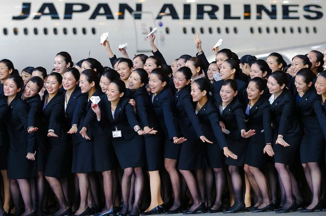 Japan Airlines new employees pose for photographs in front of a JAL aircraft during a welcoming ceremony at the company's hangar near Haneda Airport in Tokyo, Japan, on April 1, 2013. (Photo by Kiyoshi Ota/Bloomberg)
