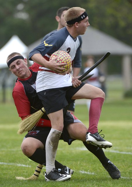 The University of Ottawa Quidditch team's Steven Kimball, front, spins away from the Silicon Valley Skrewts' Willis Miles IV during a scrimmage at the Quidditch World Cup in Kissimmee, Fla., Friday, April 12, 2013.  Quidditch is a game born within the pages of Harry Potter novels, but in recent years it's become a real-life sport.  The game is a co-ed, full contact sport that combines elements of rugby, dodgeball and Olympic handball. (Photo by Phelan M. Ebenhack/AP Photo)