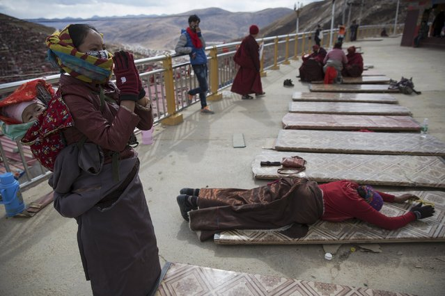 An ethnic Tibetan woman, carrying her baby on the back, prays at a monastery above the Larung Wuming Buddhist Institute, located some 3700 to 4000 metres above the sea level in remote Sertar county, Garze Tibetan Autonomous Prefecture, Sichuan province, China October 30, 2015. (Photo by Damir Sagolj/Reuters)