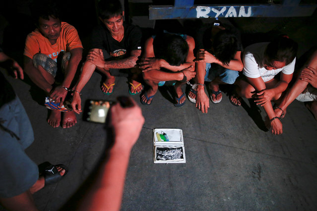 Suspects are handcuffed during a drug raid, in Manila, Philippines, October 7, 2016. (Photo by Damir Sagolj/Reuters)