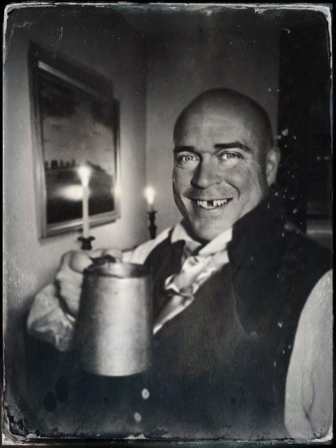 Historical reenactor Troy Kotz poses with a mug of wassail in the parlor of the Guyon-Lake-Tysen House during the annual Candlelight Tour of Historic Richmond Town, Saturday, December 13, 2014, in the Staten Island borough of New York. The annual event lets visitors experience an authentic Victorian Christmas. This image was made using the TinType by Hipstamatic iPhone app. (Photo by Chad Rachman/New York Post)