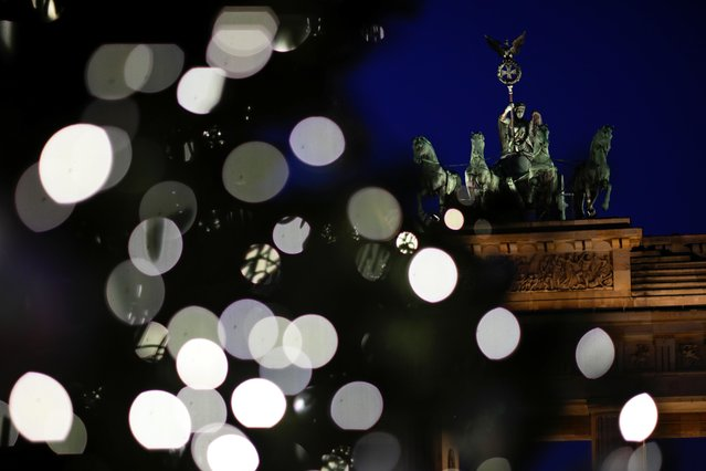 A Christmas tree is illuminated in front of Brandenburg Gate in Berlin, Germany, November 26, 2020. (Photo by Hannibal Hanschke/Reuters)