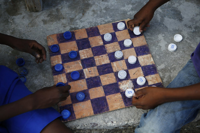 Boys play checkers with bottle caps on a homemade board in the Philanthrope neighborhood of Les Cayes, Haiti, Monday, October 17, 2016, after many homes lost their roofs and others in the seaside fishing community were completely destroyed. Some of the residents have sought shelter at nearby Philippe Guerrier high school, but they have been told they have to leave so classes can restart. (Photo by Rebecca Blackwell/AP Photo)