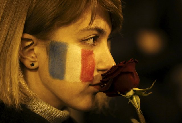 A woman with French flag painted on her face, holds a flower during a gathering in tribute to the victims of Paris attacks in Tbilisi, Georgia, November 14, 2015. (Photo by David Mdzinarishvili/Reuters)