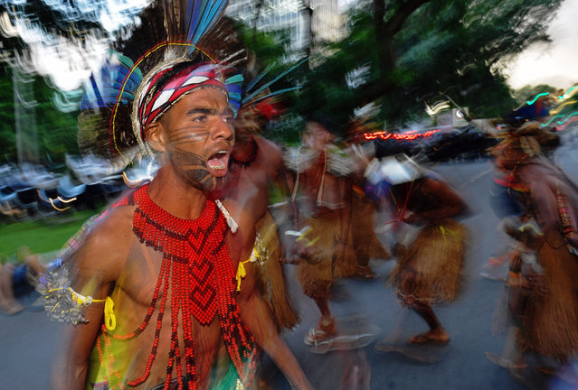 Brazilian indigenous men perform a ritual dance during a protest against the government's decision not to  recognize the land demarcation of indigenous people living in Raposa Serra do Sol, Roraima State, in Brasilia, on April 25, 2018. About 2,500 indigenous people from different tribes are taking part in the Indigenous National Mobilization (MNI) week – a mobilization which seeks to tackle territorial rights' negotiations with the government. (Photo by Carl De Souza/AFP Photo)