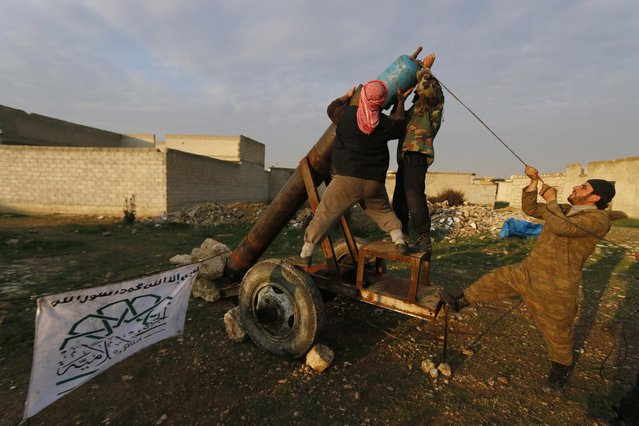 Rebel fighters of al-Jabha al-Islamiya (the Islamic Front) prepare an improvised explosive to fire towards forces loyal to Syria's President Bashar al-Assad, at the frontline near Nairab military airport in Aleppo December 30, 2014. (Photo by Hosam Katan/Reuters)