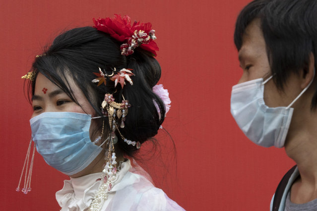 Residents wearing masks to help curb the spread the coronavirus walk along a retail street in Wuhan in central China's Hubei province, Thursday, April 9, 2020. Released from their apartments after a 2 1/2-month quarantine, residents of the city where the coronavirus pandemic began are cautiously returning to shopping and strolling in the street but say they still go out little and keep children home while they wait for schools to reopen. (Photo by Ng Han Guan/AP Photo)