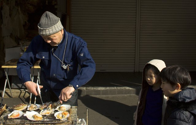 Children watch a man preparing seafood on a grill in the outer part of the Tsukiji fish market, the Jogai Shijo, in Tokyo January 4, 2015. (Photo by Thomas Peter/Reuters)
