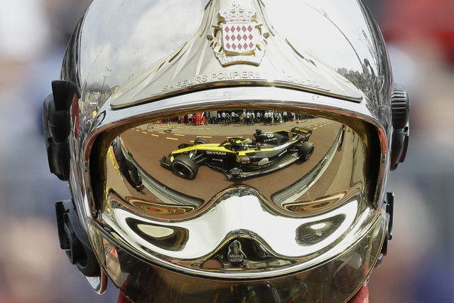 The car of Renault driver Nico Hulkenberg of Germany is reflected in a firemen's helmet visor during the first practice session for the Monaco Formula One Grand Prix at the Monaco racetrack, in Monaco, Thursday, May 24, 2018. The Monaco Grand Prix will be held on Sunday, May 27. (Photo by Claude Paris/AP Photo)