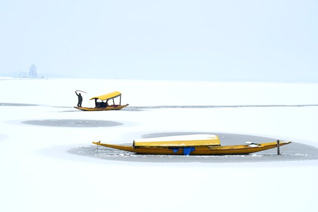 A boatman steers his boat at the partially frozen Dal Lake after a snowfall in Srinagar on January 9, 2021. (Photo by Tauseef Mustafa/AFP Photo)