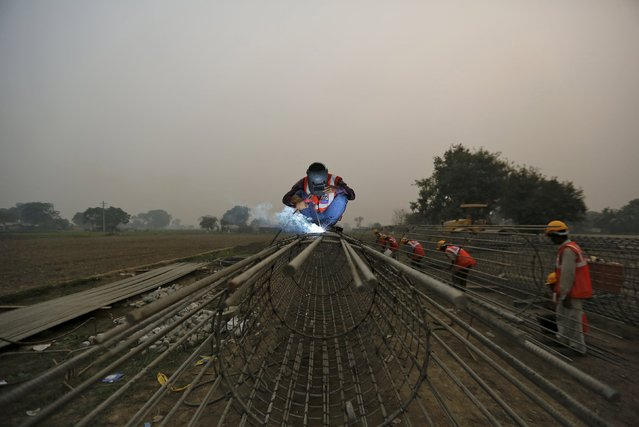 Labourers work at the construction site of a bridge being built for metro rail in New Delhi, India, November 30, 2015. (Photo by Anindito Mukherjee/Reuters)