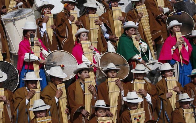 Musicians play sikus or windpipes and native drums during a ceremonial swearing-in for Bolivia's President Evo Morales, led by Aymaran spiritual guides at the archeological site Tiwanaku, Bolivia, Wednesday, January 21, 2015. (Photo by Juan Karita/AP Photo)