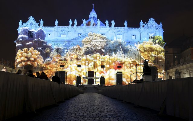 """A picture of corals, part of an art projection featuring images of humanity and climate change artistically rendered by Obscura Digital, is projected onto the facade of St. Peter's Basilica, as part of an installation entitled """"Fiat Lux: Illuminating our Common Home"""" as a gift to Pope Francis on the opening day of the Extraordinary Jubilee, at the Vatican, December 8, 2015. (Photo by Stefano Rellandini/Reuters)"""