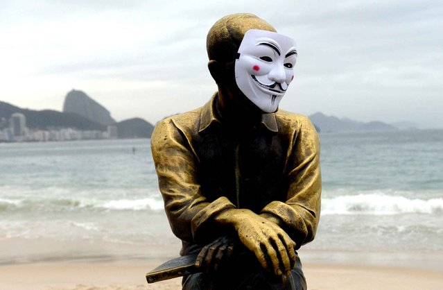 The statue of Brazilian poet Carlos Drummond de Andrade on Copacabana Beach with a Guy Fawkes mask, on June 23, 2013. (Photo by Yasuyoshi Chiba/AFP Photo)