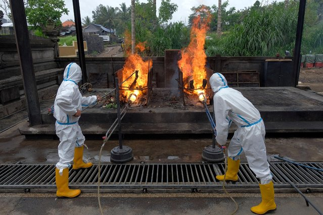 Officials wearing personal protective equipment (PPE) set fires to bodies of people who died due to the coronavirus at a crematorium in Bangli, Bali, Indonesia October 10, 2020. (Photo by Nyoman Hendra Wibowo/Antara Foto via Reuters)