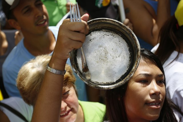 An opposition supporter hits an empty pot during a protest march against shortages of basic goods in Caracas January 24, 2015. (Photo by Jorge Silva/Reuters)