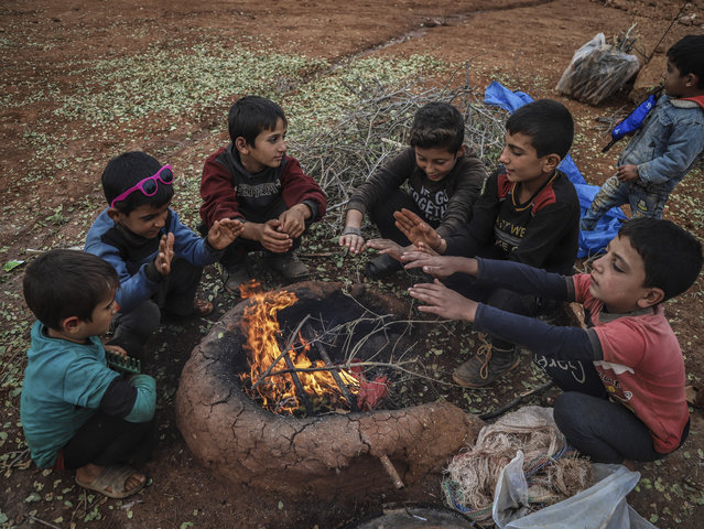Kids are seen around a tent as Syrians set a fire in a tent by using dangerous materials to keep the family members warm due to cold winter conditions at a refugee camp in Idlib, Syria on January 11, 2021. Syrians have no other options to burn in tents apart from clothes, plastic wastes and other materials which jeopardize their health by causing mainly asthma, bronchitis and other disease in order to keep the families warm amid cold weather. (Photo by Muhammed Abdullah/Anadolu Agency via Getty Images)