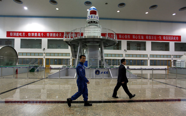 Chinese astronauts Fei Junlong (left) and Yang Liwei walk past training simulation equipment during a media tour of the China Astronaut Center at Beijing Aerospace City, on April 29, 2011. (Photo by David Gray/Reuters via The Atlantic)