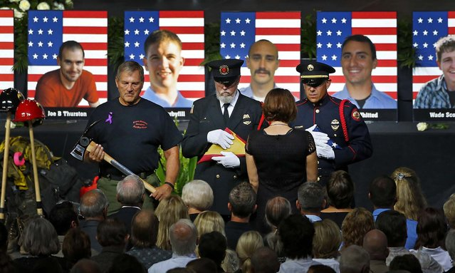 An honor guard presents families with American flags during a memorial service at Tim's Toyota Center in Prescott Valley, Arizona, on July 9, 2013. 19 firefighters of the Granite Mountain Hotshots crew died battling a fast-moving wildfire on June 30. (Photo by David Kadlubowskil/Getty Images)
