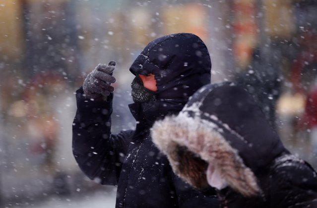 A man covers his face from heavy falling snow as he makes his way through Times Square in New York January 26, 2015. (Photo by Mike Segar/Reuters)