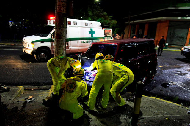 Comandos de Salvamento rescuers try to disconnect a car battery to avoid risk of fire after a car accident in San Salvador, El Salvador July 17, 2016. (Photo by Jose Cabezas/Reuters)