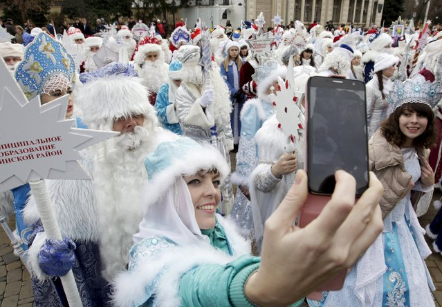 Participants take a selfie while people, dressed as Ded Moroz, his granddaughter Snegurochka and other characters, participate in a festive pre-holiday procession in Krasnodar, southern Russia, December 19, 2015. Ded Moroz (Old man Frost or Grandfather Frost) and Snegurochka (Snow Maiden) are the main characters of the New Year and Christmas holidays celebration in Russia and some other former Soviet states. (Photo by Eduard Korniyenko/Reuters)