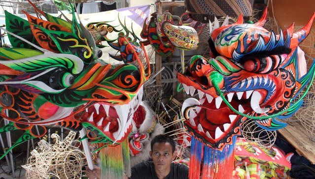 An Indonesian worker checks two dragon masks he made for the upcoming Lunar New Year at a traditional Chinese dragon and lion masks and custome maker in Bogor, Indonesia, 02 February 2015. (Photo by Adi Weda/EPA)