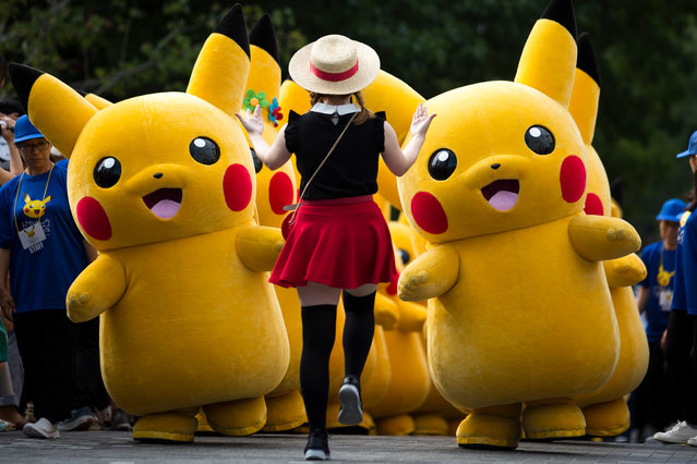 Performers dressed as Pikachu, a character from Pokemon series game titles, march during the Pikachu Outbreak event hosted by The Pokemon Co. on August 10, 2018 in Yokohama, Kanagawa, Japan. (Photo by Tomohiro Ohsumi/Getty Images)