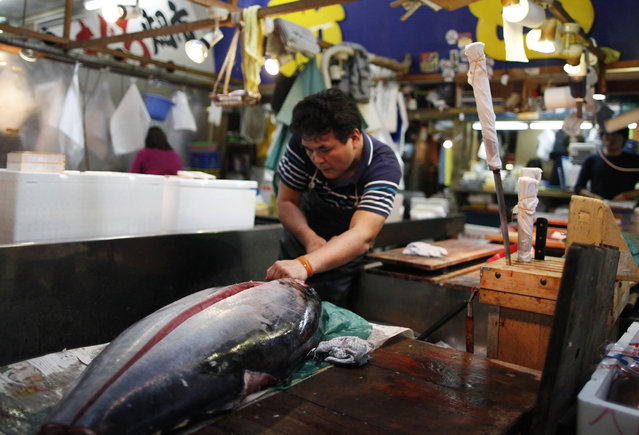 In this June 25, 2015 file photo, a dealer cuts tuna in Tsukiji fish market in Tokyo. It's among the biggest of Japan's many New Year holiday rituals: Early on Tuesday, January 5, 2016, a huge, glistening tuna will be auctioned for a lot of money at Tokyo's 80-year-old Tsukiji market. Next year, if all goes as planned, the tradition won't be quite the same. (Photo by Shuji Kajiyama/AP Photo)