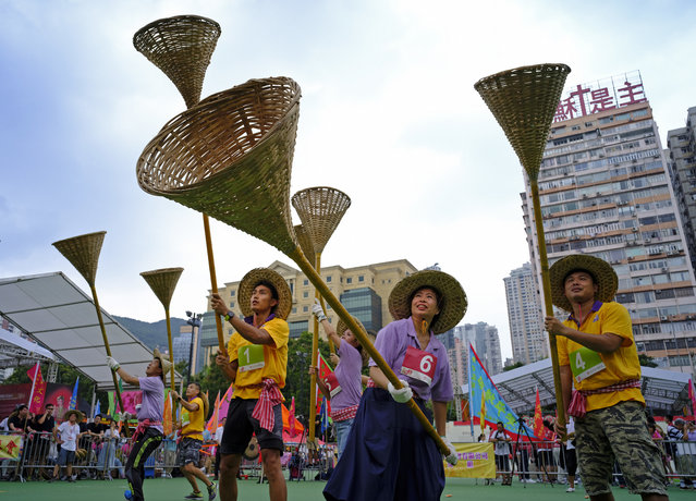 "Participants try to catch rice in small orange color bags with baskets on sticks during the Ghost Grappling competition to mark the ""Hungry Ghost Festival"" at a downtown park in Hong Kong Sunday, August 26, 2018. Countless hungry and restless ghosts are roaming Hong Kong, and the world, to visit their living ancestors, at least according to Chinese convention. In traditional Chinese belief, the seventh month of the lunar year is reserved for the Hungry Ghost festival, or Yu Lan, a raucous celebration marked by feasts and music. (Photo by Vincent Yu/AP Photo)"