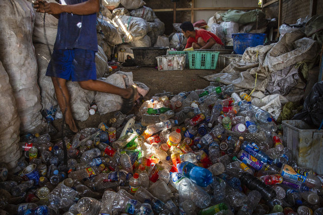 A man separates different kinds of plastic, which he will later sell, recycled from the Citarum river on August 28, 2018 outside Bandung, Java, Indonesia. (Photo by Ed Wray/Getty Images)