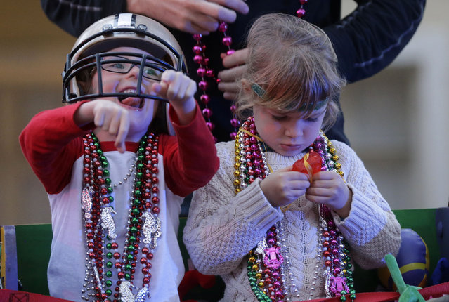 Barker Curry, 4, cheers to floats for beads and trinkets, while his cousin Sophia Curry, 3, right, looks at one of her trinkets, during the Krewe of Proteus Mardi Gras parade in New Orleans, Monday, February 16, 2015. (Photo by Gerald Herbert/AP Photo)