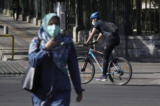 Wearing protective face masks to help prevent the spread of the coronavirus, a man rides his bicycle and a woman crosses a street in downtown Tehran, Iran, Monday, April 5, 2021. Iran's capital is once again under a code red status, the highest level of restrictions imposed to curb the spread of the coronavirus as the country struggles with a new surge in daily deaths. (Photo by Vahid Salemi/AP Photo)