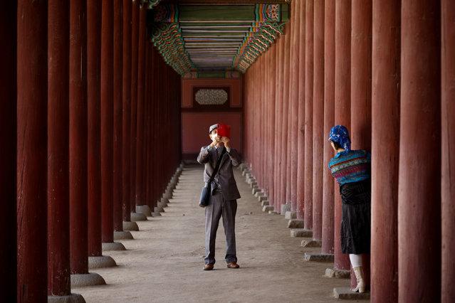 A man wearing a protective mask photographs his wife amid the coronavirus disease (COVID-19) pandemic at the Gyeongbok palace in Seoul, South Korea, May 3, 2021. (Photo by Kim Hong-Ji/Reuters)