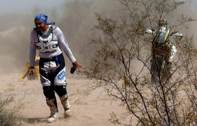 Yamaha rider Alberto Sebastian Urquia of Argentina walks before being picked up by an assistance helicopter and leaving his motorcycle on the road during the ninth stage of the Dakar Rally 2016 near Belen, Argentina, January 12, 2016. The Husqvarna motorcycle on the right belongs to Hans Smit of Netherlands, who was also taken back to the bivouac on a helicopter. (Photo by Marcos Brindicci/Reuters)