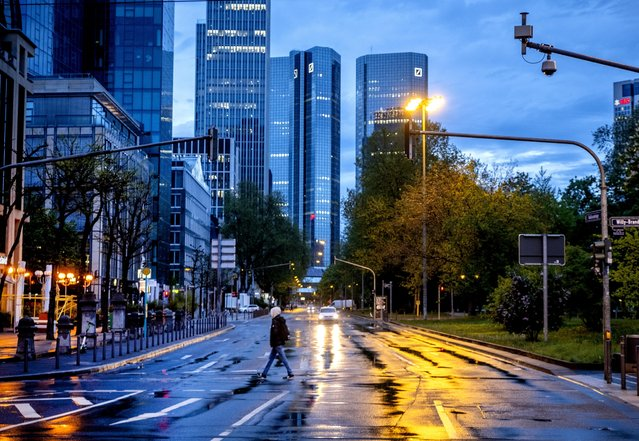 A man crosses a street shortly after the end of the curfew in central Frankfurt, Germany, Tuesday, May 11, 2021. (Photo by Michael Probst/AP Photo)