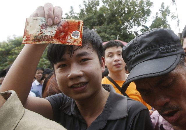 A man shows a banknote smeared with pig blood during a festival at the Nem Thuong village in Bac Ninh, north of Hanoi, February 24, 2015. (Photo by Reuters/Kham)