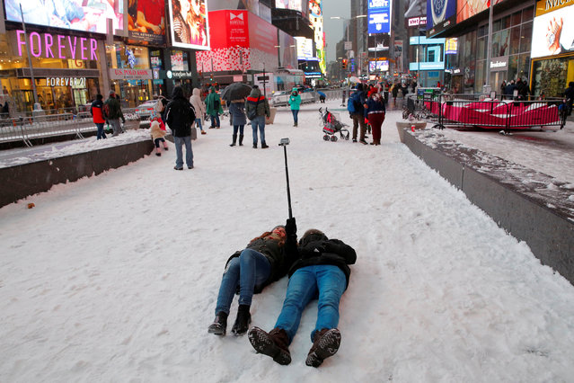 People take a selfie during morning snow in Times Square, Manhattan, New York City, U.S. December 17, 2016. (Photo by Andrew Kelly/Reuters)