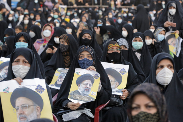 """Women supporters of Iranian presidential candidate Ebrahim Raisi hold up his posters during an election campaign rally in the city of Eslamshahr, about 25 kilometres south of the centry of the capital Tehran, on June 6, 2021. The 60-year-old ultra-conservative Raisi, widely seen as the favourite to win the June 18 presidential election, heads the judiciary and is a """"hodjatoleslam"""", one rank below that of ayatollah in the Shiite clerical hierarchy. (Photo by AFP Photo/Stringer)"""