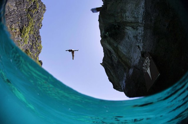 In this handout image provided by Red Bull, Artem Silchenko of Russia dives from the 27 metre platform at Maya Bay in the Andaman Sea during the final stop of the 2013 Red Bull Cliff Diving World Series on October 22, 2013 at Phi Phi Island, Thailand. (Photo by Samo Vidic/Red Bull via Getty Images)