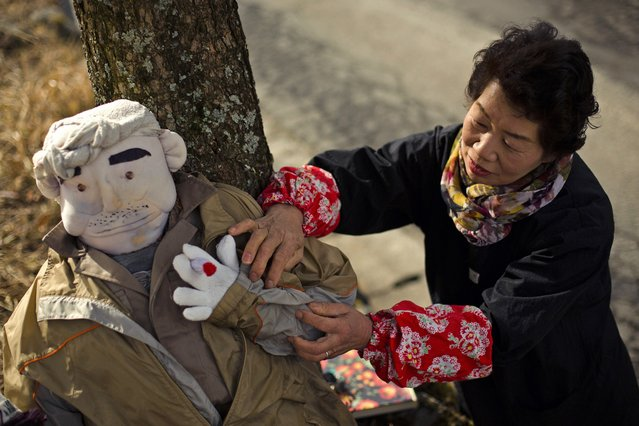 Tsukimi Ayano arranges a scarecrow, which represents her father, in the mountain village of Nagoro on Shikoku Island in southern Japan February 24, 2015. (Photo by Thomas Peter/Reuters)