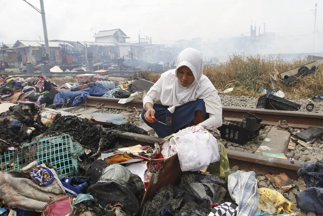 A girl searches through debris following a fire in a slum area next to railway tracks in Kampung Bandan, North Jakarta, Indonesia January 26, 2016 (Photo by Garry Lotulung/Reuters)