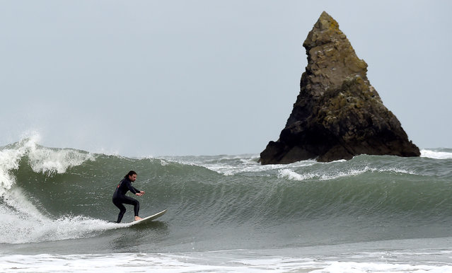 A surfer attempts to ride large waves near Church Rock, Broad Haven, Pembrokeshire, Wales on September 19, 2018. (Photo by Rebecca Naden/Reuters)