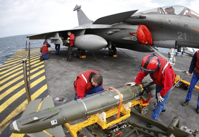 Red jacket ordnance crew place bombs under a Rafale fighter jet aboard France's Charles de Gaulle aircraft carrier on mission in the Gulf, January 28, 2016. (Photo by Philippe Wojazer/Reuters)