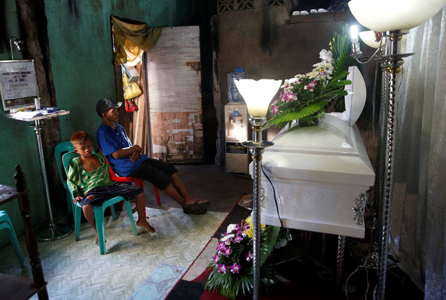 The father and younger brother of Jonel Segovia mourn near his coffin after Jonel was shot dead by suspected vigilantes at a house storing illegal narcotics, police said on Thursday, in Caloocan city, Metro Manila, in the Philippines December 29, 2016. (Photo by Erik De Castro/Reuters)